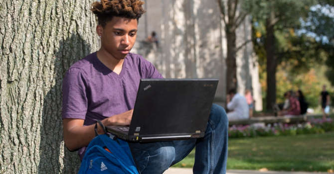 Transfer student on lawn with laptop